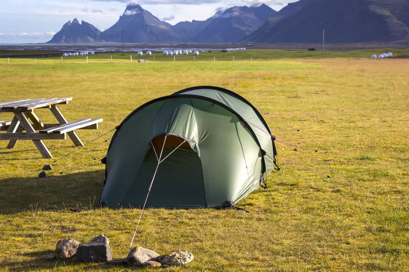 Lonely Camping site with a tent in Iceland. Green Iceland Landscape_Collection Zeltplatz Adventure Beauty In Nature Camping Day Field Freedom Tower Grass Landscape Meadow Mountain Nature No People North Outdoors Scenery Scenics Table Tent Vestrahorn Wildlife Zelten