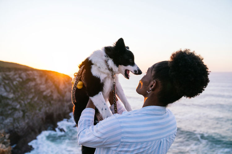 Man with dog against sky during sunset