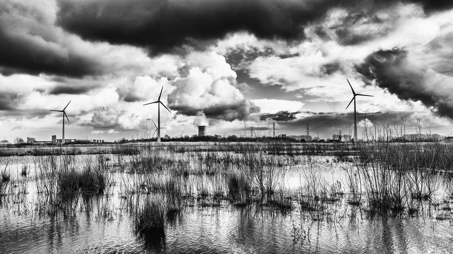Low angle view of windmills in front of river against cloudy sky