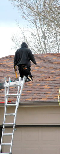 Rear view of man working on roof against building