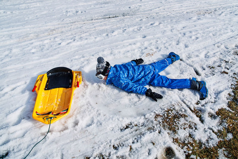 High angle view of man lying on snow covered land