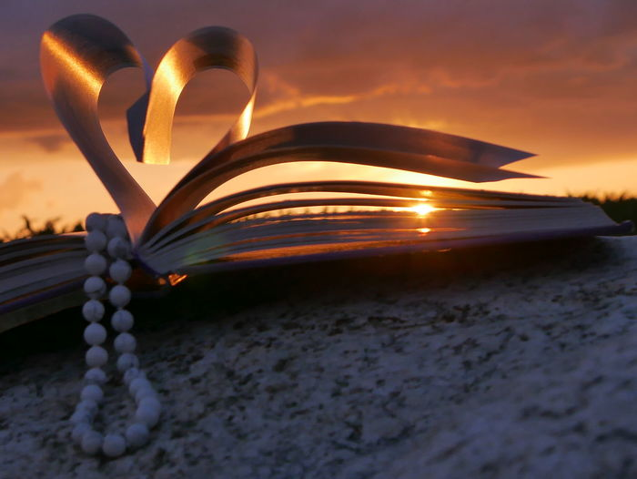 Bead necklace with heart shape folded pages of book during sunset