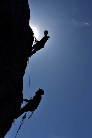 Low angle view of silhouette men climbing mountain against clear sky