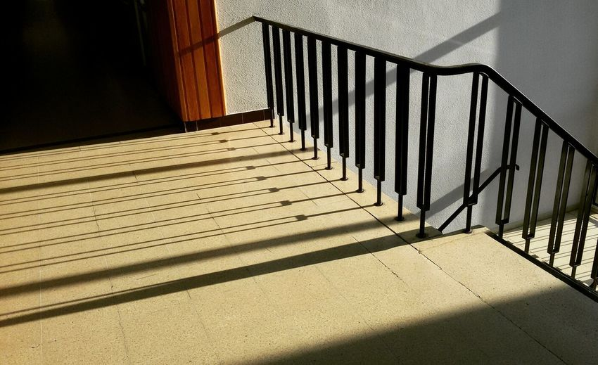 Shadow Of Railing On Tiled Floor In School