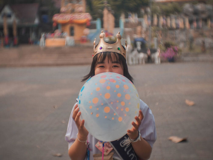 Portrait of young woman holding balloon while standing on road