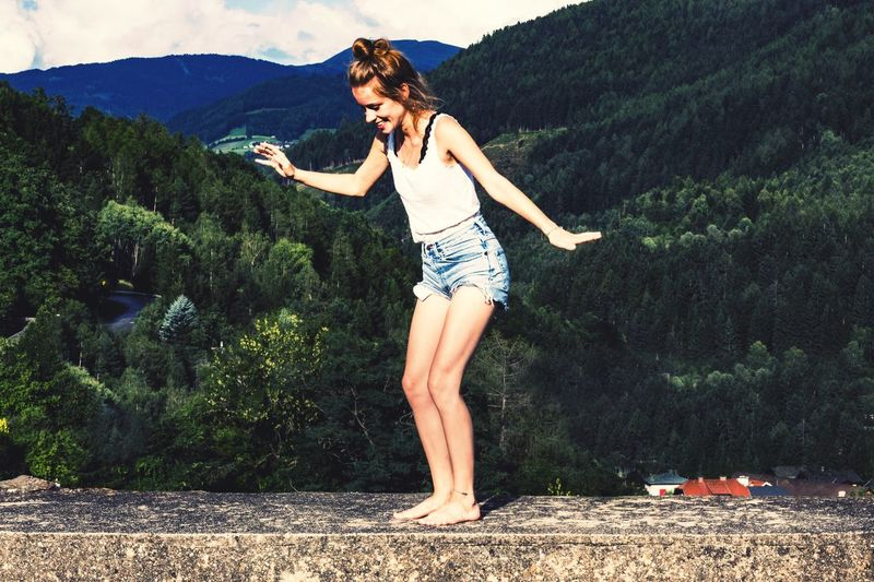 Full length of young woman standing against mountains