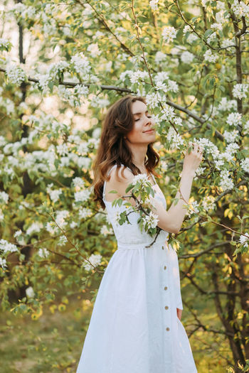 A cute happy young woman with a hairstyle in a white dress is walking enjoying nature in the summer