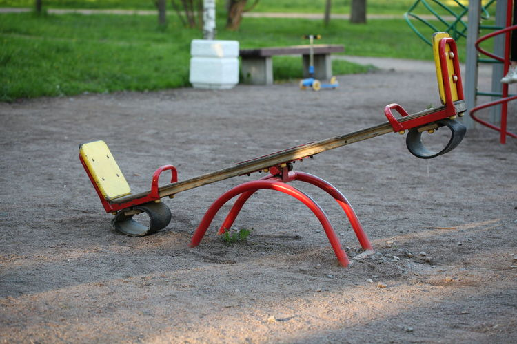 Childhood Park Playground Day Absence Park - Man Made Space Focus On Foreground Empty Seesaw Metal Nature Red Outdoors Outdoor Play Equipment Transportation Grass Merry-go-round Bicycle Land Wheel Park Bench