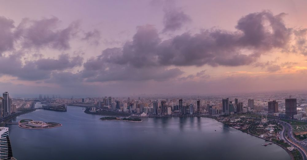 Panoramic View Of River And Buildings Against Sky At Sunset