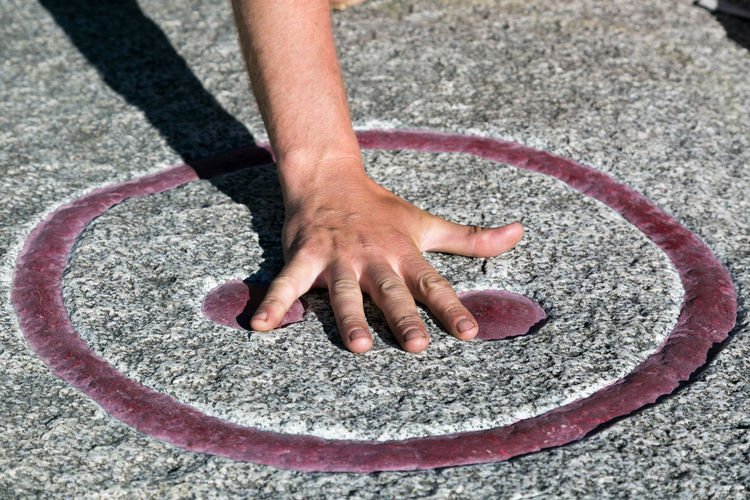 Cropped hand of man touching symbol on floor
