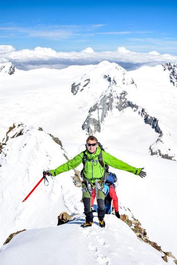 Full length portrait of male hiker on snowcapped mountain against sky