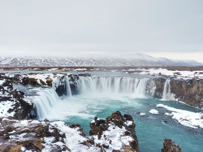 Scenic view of waterfall godafoss against sky during winter