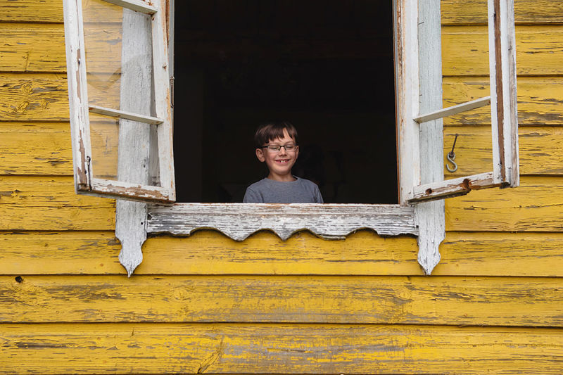 Portrait of smiling woman against yellow window