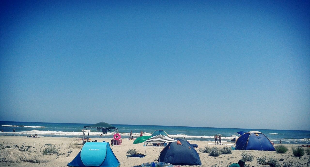 beach, sea, copy space, blue, sand, water, clear sky, horizon over water, nature, day, vacations, tranquility, no people, nautical vessel, sunlight, scenics, outdoors, tent, sky, beauty in nature