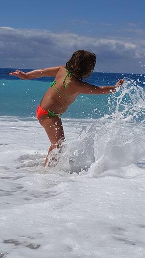 Girl splashing water in sea against sky