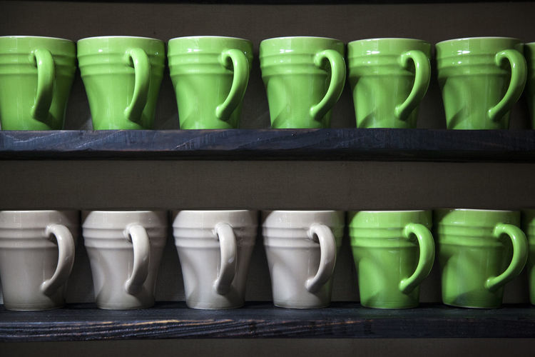 Green and white cups on wooden shelves