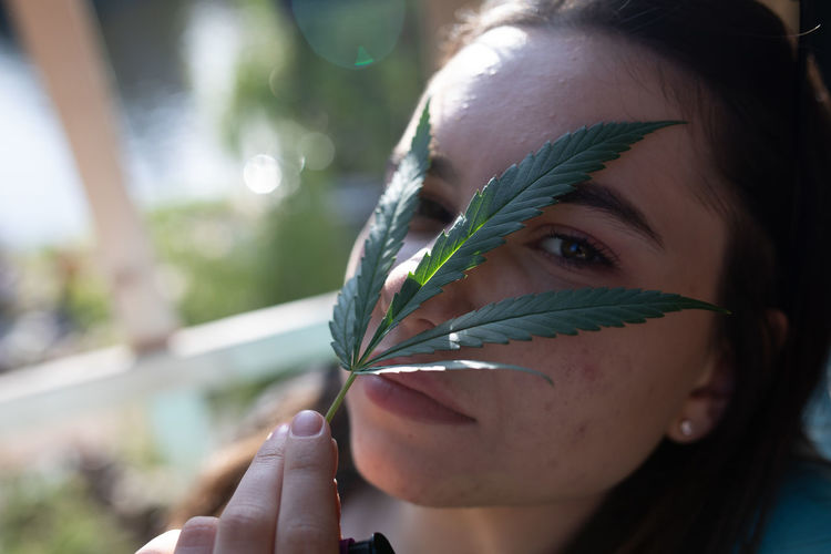 Close-up portrait of young woman holding leaves over face