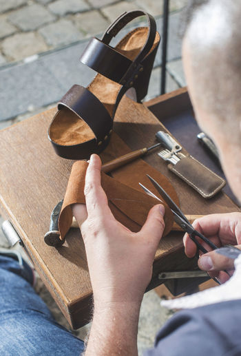 Shoes Shoemaker Craft Leather Hands Handmade Work Tools Real People One Person Holding Human Hand Hand High Angle View Men Work Tool Working Human Body Part Occupation Skill  Day Tool Hand Tool Lifestyles Art And Craft Sitting