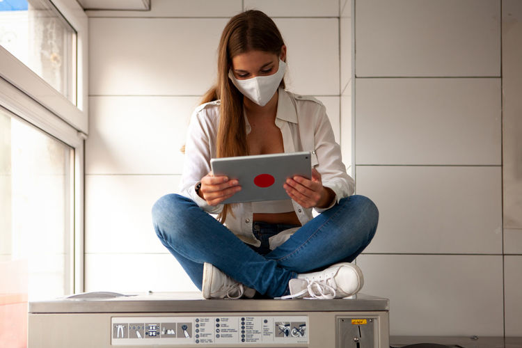 Young woman wearing a protective mask sitting on a big washing machine and using a tablet.