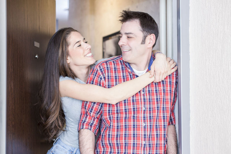 Smiling Woman Embracing Man While Standing Against Door