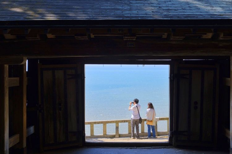 Rear View Of Couple Overlooking Calm Blue Sea