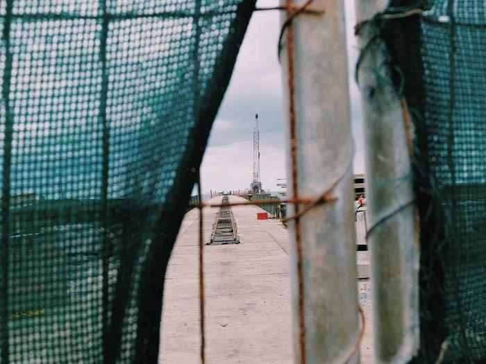 Pier against sky seen through net