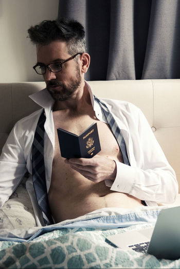 Mature man holding passport while sitting on bed