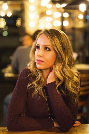 Beautiful Woman Blond Hair Close-up Focus On Foreground Illuminated Incidental People Indoors  Leisure Activity Lifestyles Looking At Camera Night One Person Portrait Real People Restaurant Sitting Young Adult Young Women