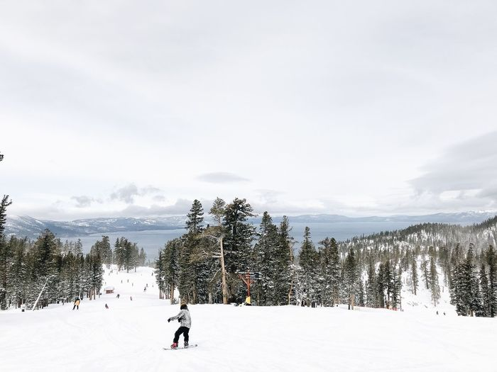 Man snowboarding on snow covered field against sky