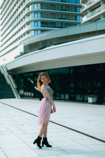 Full length portrait of woman standing against building in city