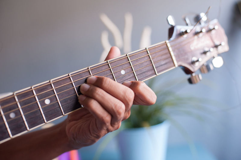 Cropped hand playing guitar at home