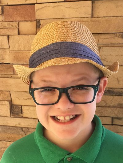 Portrait Of Smiling Boy Wearing Hat And Eyeglasses Against Wall