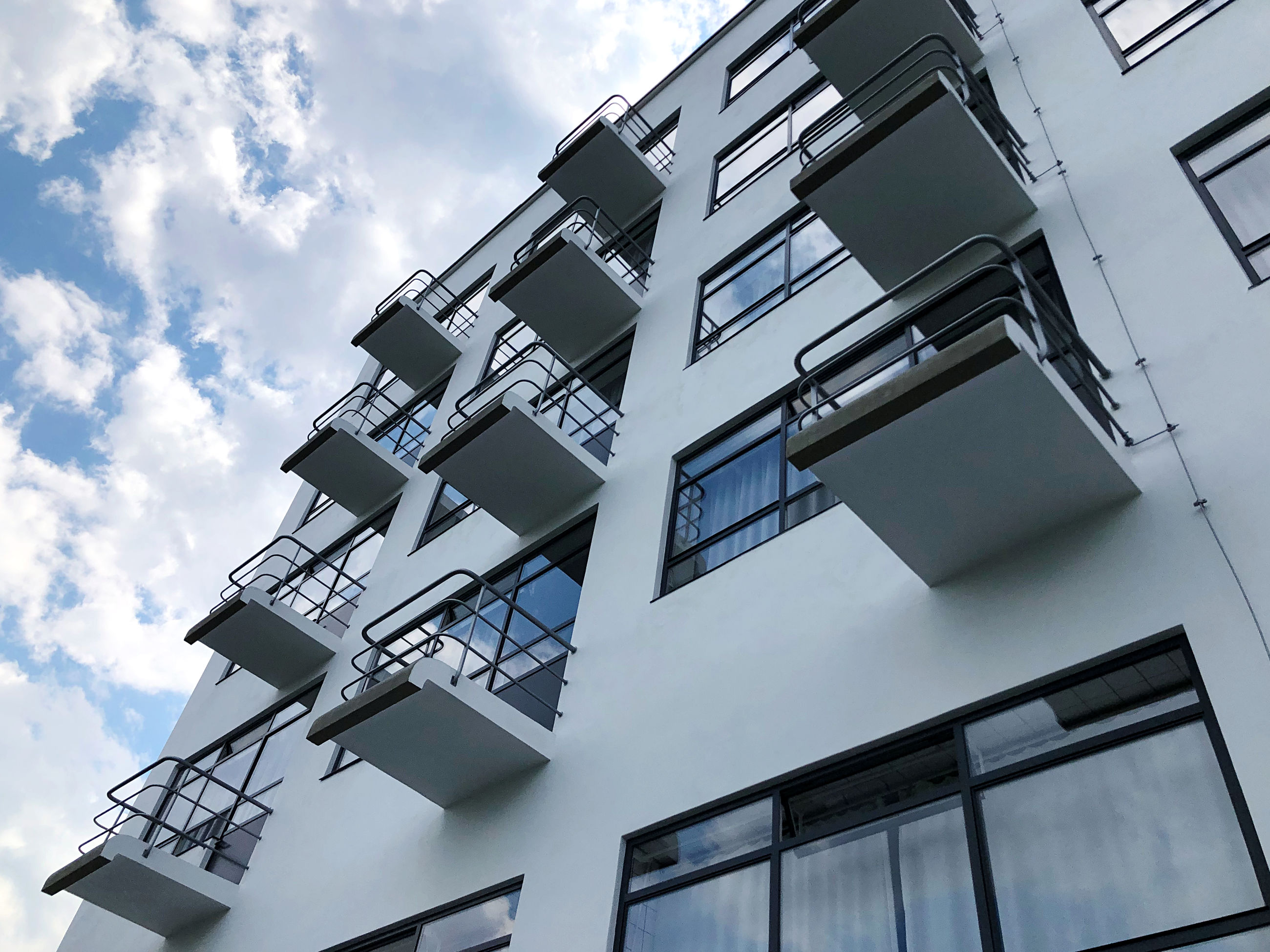 architecture, built structure, building exterior, sky, low angle view, building, cloud, facade, tower block, window, city, house, no people, residential district, blue, staircase, skyscraper, daylighting, nature, apartment, outdoors, day