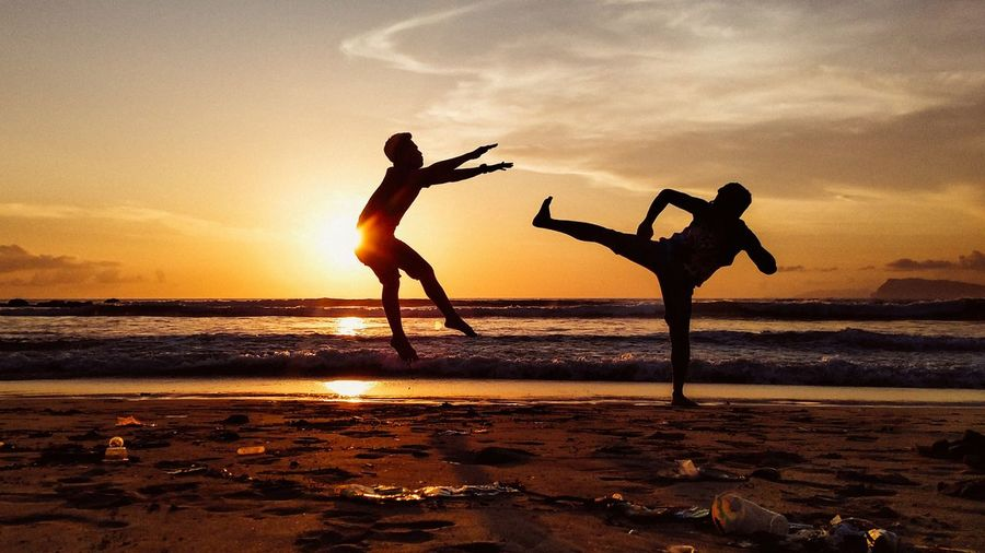 Silhouette people fighting at beach against sky during sunset