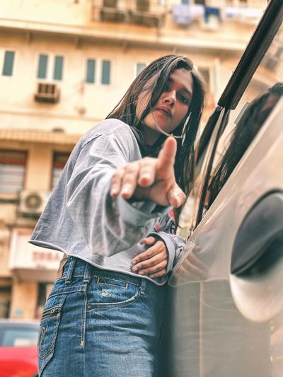 Portrait of woman gesturing standing by car in city