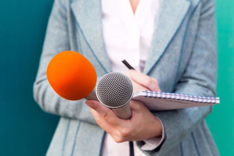 Reporter at media event. Press conference. Audio Broadcasting Close-up Communication Conference Event Holding Human Hand Information Interview Journalism Journalist Live Media Microphone Nootebook Pen Press Radio Speech Tv Writing