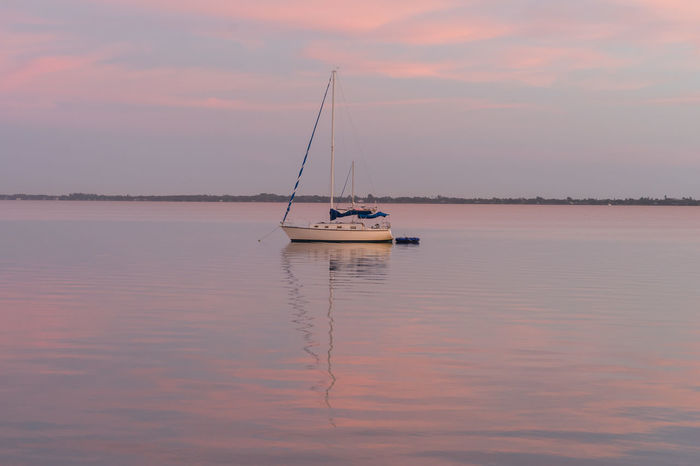 A Sailboat at Sunrise Indian River Indian River Lagoon Sunset Melbourne, Florida Cloud - Sky Colorful Sky Mast Nature Nautical Vessel No People Outdoors Reflection Sailboat Sea Sky Sunrise Sunset Transportation Water Waterfront