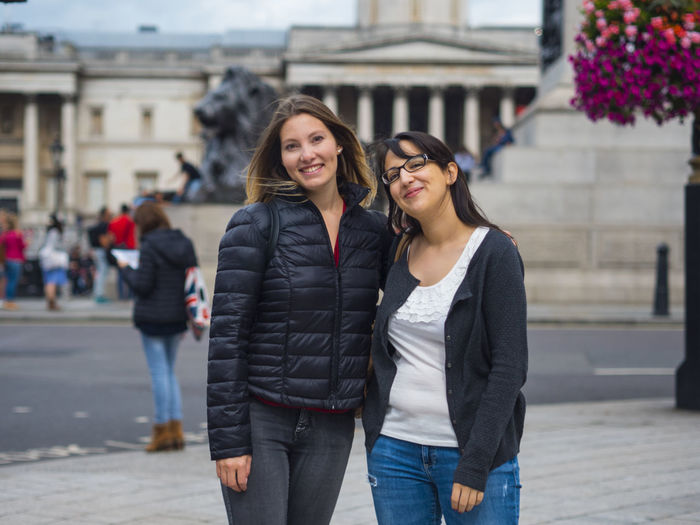 Portrait of smiling female friends standing in city