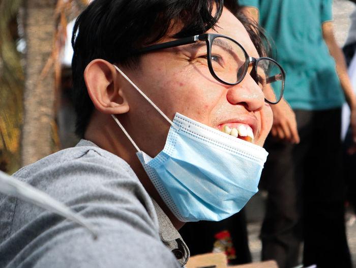 Close-up portrait of man holding eyeglasses