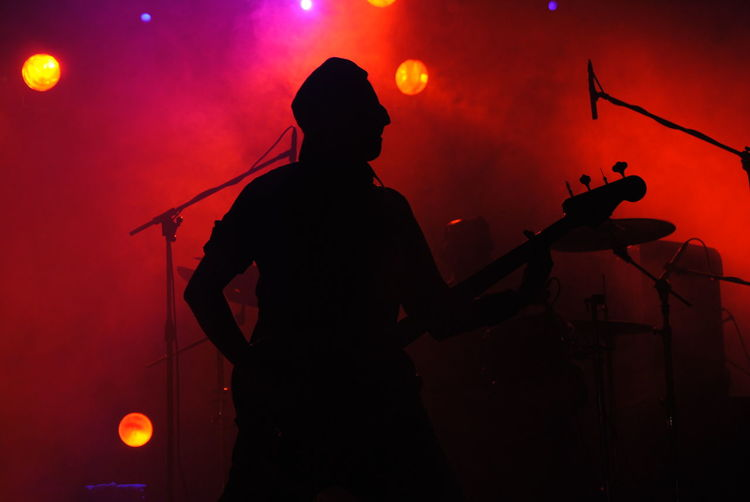 Silhouette Man Playing Guitar At Music Concert