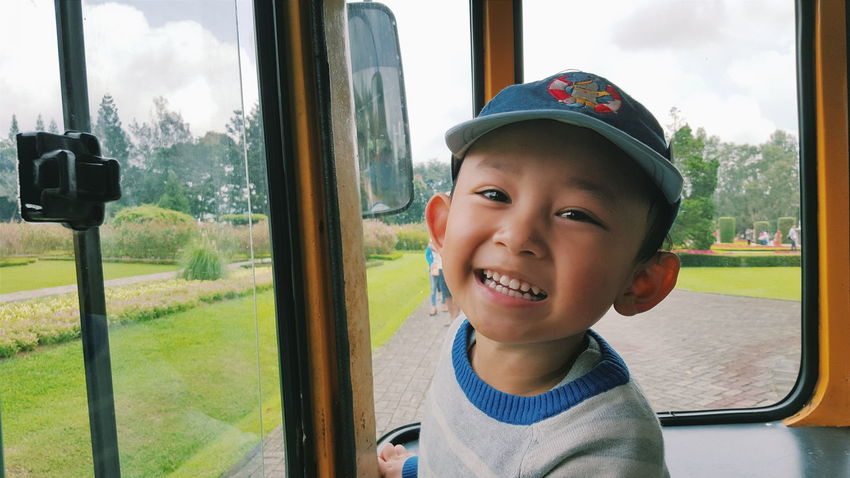Boy Cap Casual Clothing Close-up Cute Day Grass Hat Headshot Lawn Leisure Activity Lifestyles Person Portrait Sky Smile Toddler  Toothy Smile Vehicle Interior Window Happy Smiling The Portraitist - 2016 EyeEm Awards My Commute