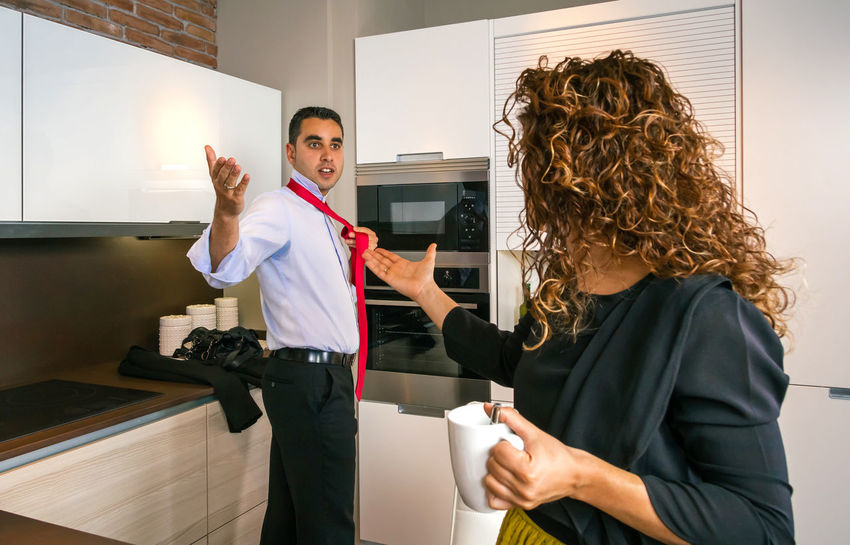 Angry young businessman arguing with curly woman at home while knotting his tie 30s Angry Breakfast Busy Couple Discussing Food And Drink Home Horizontal Morning Orange Rush Stress Tablet Woman Worker Businessman Businesswoman Caucasian Kitchen News Problem Quarrel Technology Time