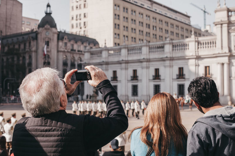 Rear view of people photographing buildings in city