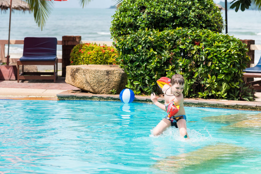 Trat, Thailand - May, 21, 2017 : Unidentified name Boys swimsuit floating and playing with ball in the swimming pool at Klong Prao Resort in Prao Beach Koh Chang island Trat, Thailand. Day Editorial  Enjoyment Full Length Fun Illustrative Illustrative Editorial Leisure Activity Nature One Person Outdoors People Real People Sky Summer Swimming Swimming Pool Thailand Tree Vacations Water Young Adult Young Women
