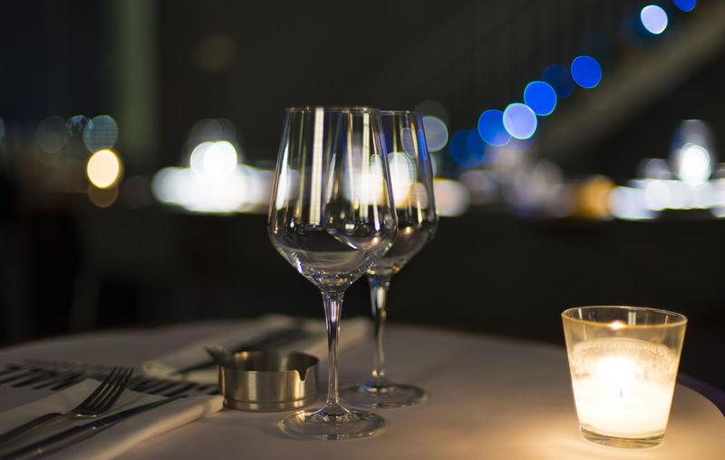 Close-up of wine glasses on illuminated table