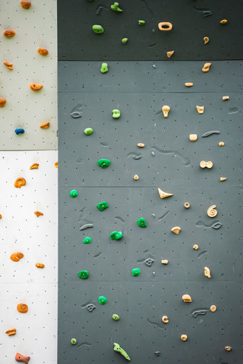 Abstract colorful of rock climbing wall with toe and hand hold studs., various colored grips at gym