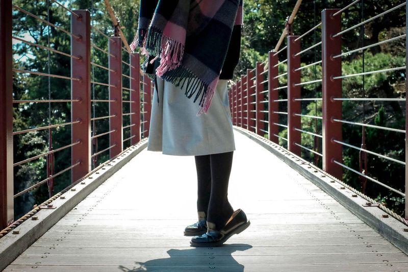 Low section of woman tiptoeing on footbridge