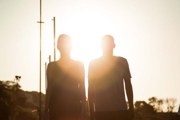 Low Angle View Of Man And Woman Standing Against Sun