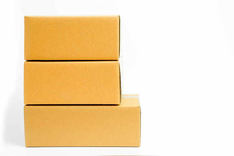 Cardboard boxes stacked with copy space on isolated white background. Start small business concept. Background Blank Board Box Brown Business Cardboard Cargo Carton Container Copy Delivery Detail Empty Environment Fragile Freight Gift House Industry Interior Isolated Mail Moving New Object Office Pack Package Packaging Paper Parcel Personal Pile Post Real Send Shipping  Space Stack Storage Store Table Text Transport Transportation Warehouse White Wooden