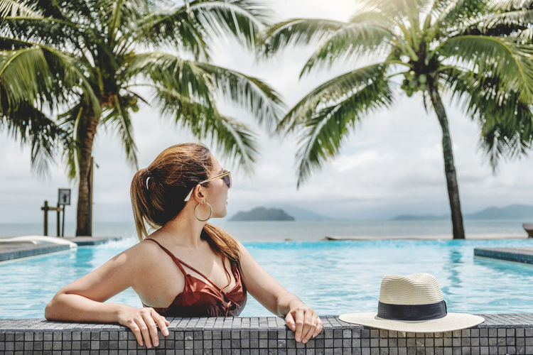 Woman relaxing at swimming pool against palm trees
